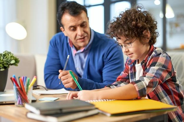 中年のラテン系の父親が家の机に一緒に座っている間、彼の息子、学童と宿題について話し合うのを手伝っています。オンライン学習、家族、父性の概念