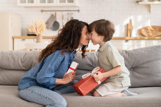돌보는 엄마와 아들은 소파에 앉아 선물을 들고 사랑스러운 작은 아이가 선물을 교환합니다.