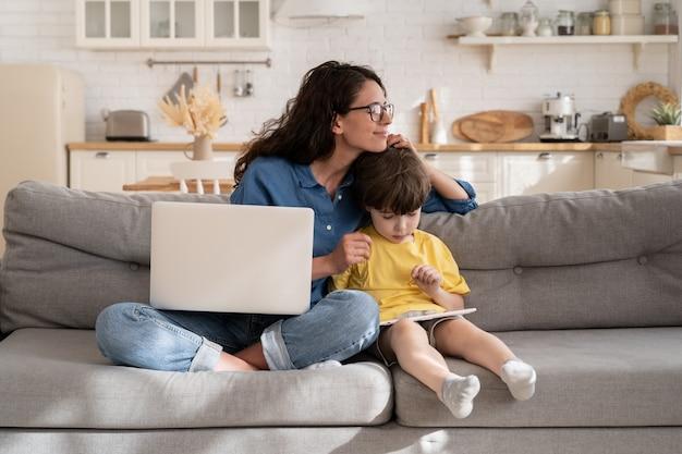 デジタルタブレットで遊ぶ検疫抱擁息子に自宅で仕事をして幸せな思いやりのあるお母さん