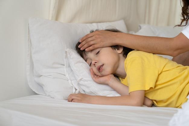 思いやりのあるお母さんは、発熱とインフルエンザの後にベッドで寝ている平和な少年の子供の体温に触れる額をチェックします