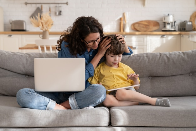 Caring mom help preschool kid with elearning on digital tablet as work on laptop computer from home