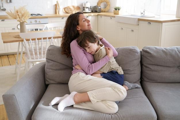 思いやりのある母親と就学前の子供の男の子は、目を閉じて家族の愛と絆で抱き締めてソファに座っています