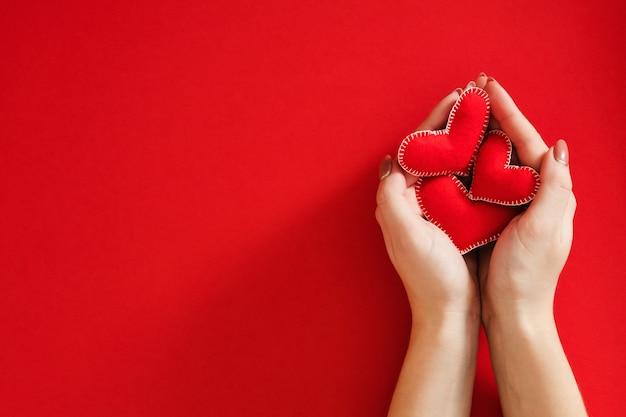 Заботливая мама. семейное понятие. вид сверху нежных женских рук, держащих сердечки из фетра ручной работы над красным