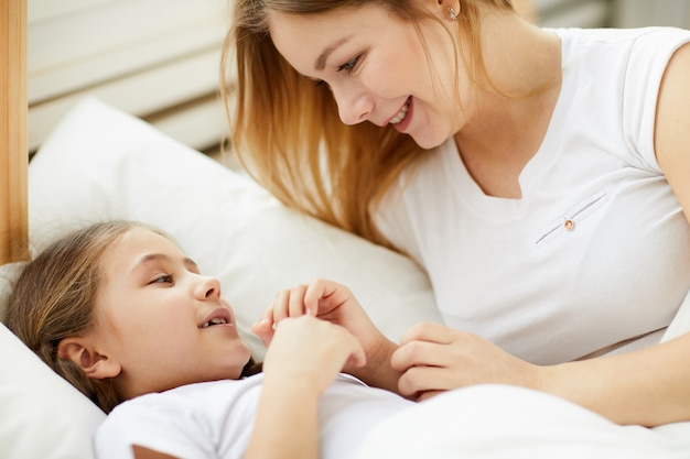Заботливая мать укладывает дочь спать