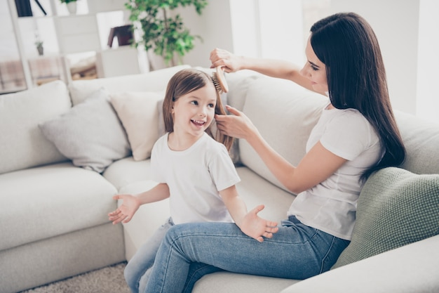 Caring mother make her small daughter hairdo in house