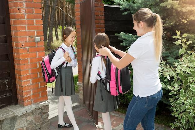 思いやりのある母親が娘たちを学校に見送ります