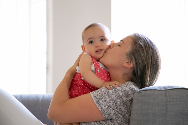 Madre premurosa che si siede sul divano e bacia la sua piccola figlia con amore. adorabile bambina a. mummia caucasica dai capelli lunghi che tiene neonato con entrambe le mani. concetto di famiglia e maternità