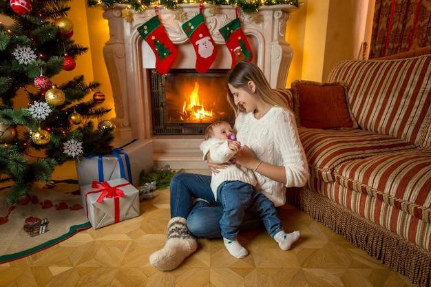 Заботливая мать сидит со своим мальчиком у камина в канун рождества