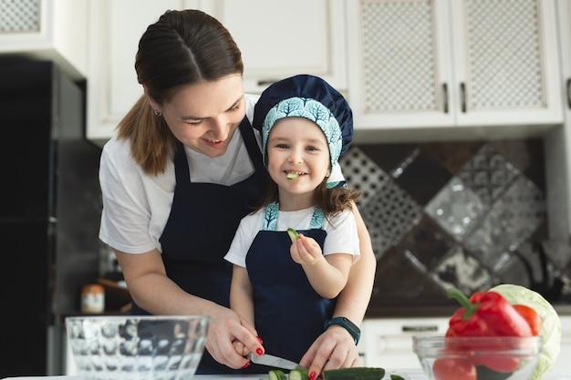 Заботливая мать учит маленькую дочь готовить салат на кухне, молодая мама и очаровательная милая девочка в фартуке измельчают овощи с ножом на столешнице, стоя на кухне дома