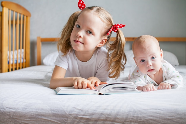 A caring older sister is reading a book to her younger newborn sister while lying on the bed