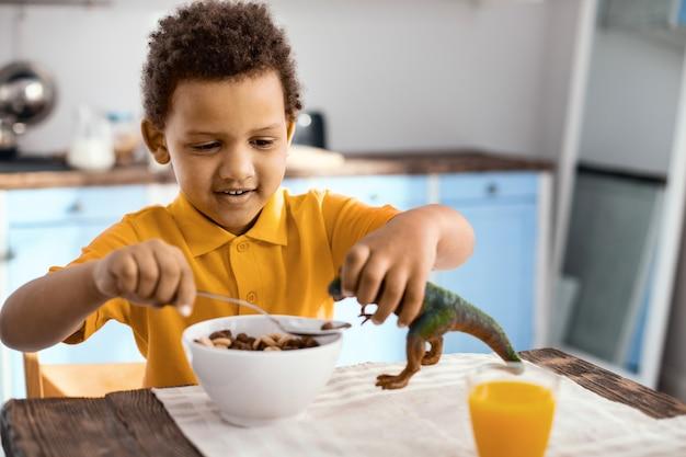 Заботливый хозяин. жизнерадостный мальчик сидит за кухонным столом и завтракает, давая кашу в пищу своему игрушечному динозавру