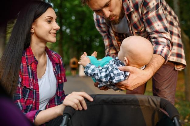 여름 공원에서 산책하는 작은 아기와 함께 돌보는 부모