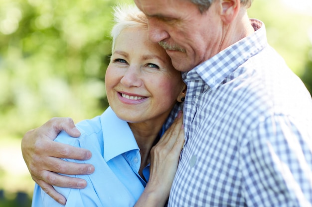 Caring senior couple embracing in park