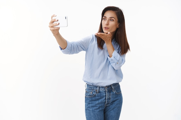 다정하고 예쁜 성인 아내는 스마트폰 화상 통화, 말하는 파트너, 시시덕거리는 셀카 찍기, 휴대전화를 불고, 전면에 가제트 디스플레이를 보고, 흰색 벽에 서서 키스를 보냅니다.