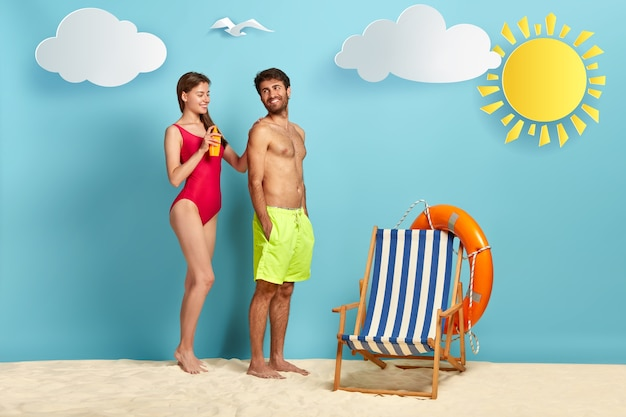 Caring wife appiles suncream on husband back for skin protection during sunbathing
