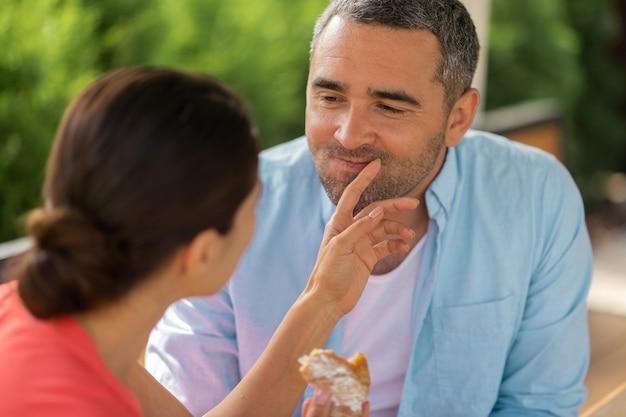 思いやりのある妻。おいしいクロワッサンを与えながら夫の世話をしている黒髪の妻