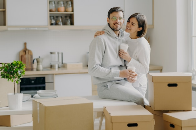 Caring woman embraces husband with love, drink takeaway coffee, pose in modern kitchen with unpacked boxes around, move into new apartment for living, rent flat, unpack belongings, have break