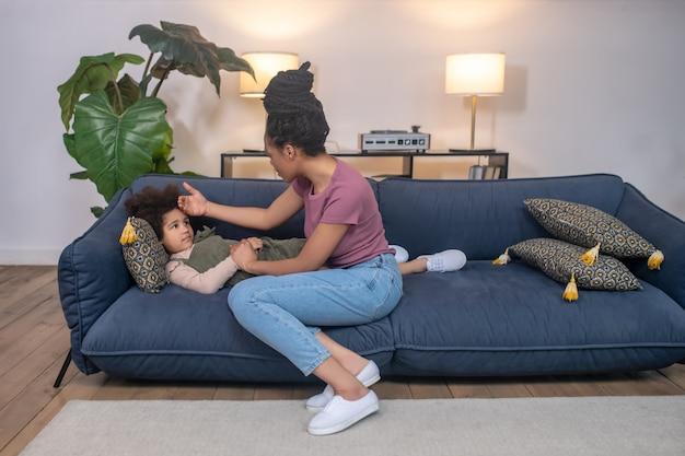 배려, 걱정. 파란 소파에 누워 피곤한 어린 딸 옆에 앉아 높은 헤어스타일을 가진 걱정스러운 아프리카계 미국인 여성