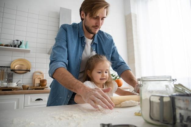 思いやりのある若い白人の父とかわいい小さな未就学児の娘が一緒に自宅のキッチンで焼く、幸せな愛情のあるお父さんは小さな女の子の子供に料理を教え、朝食用のパンケーキやビスケットを準備します