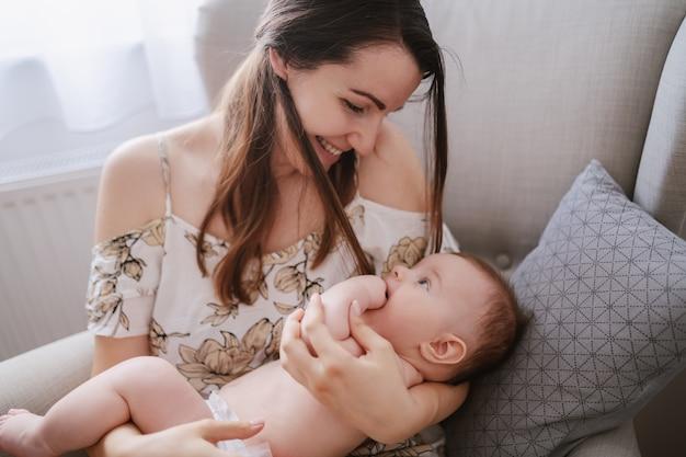肘掛け椅子に座りながら腕を組んで彼女の生後6ヶ月の息子を保持している思いやりのある若い白人の母。赤ちゃんの母親の目を見て、指を口の中に入れます。