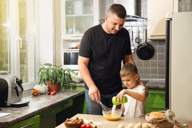 思いやりのある若い父親は、小さな未就学児の息子がクッキーを準備するのを助けます
