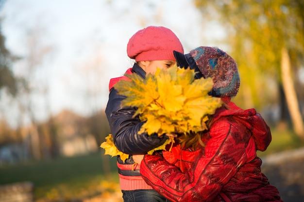 思いやりのある若い母親は、晴れた暖かい日に黄色いカエデの葉の花束を持って秋の公園を歩いている間、彼女の小さな娘にキスして抱擁します。家族の愛とケアの概念