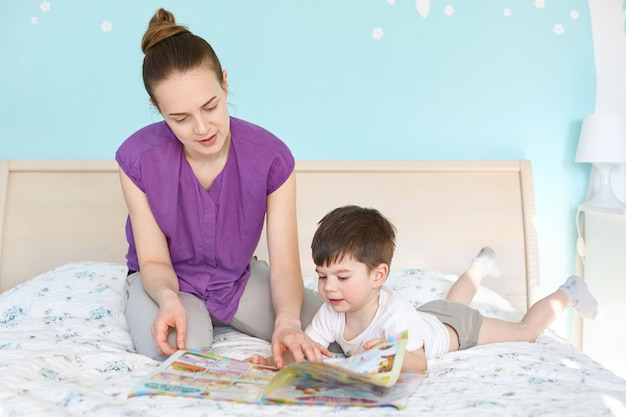 Caring young mother reads magazine with pictures for children to her small son