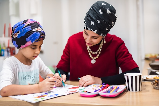 Caring young mum or nanny helping cute kid daughter teaching toddler child daughter drawing picture with pencils, learn creative art activity at home