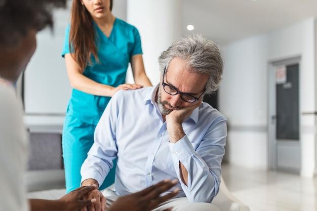 Заботливая молодая женщина-врач утешает нездорового зрелого пациента в депрессии на встрече в больнице