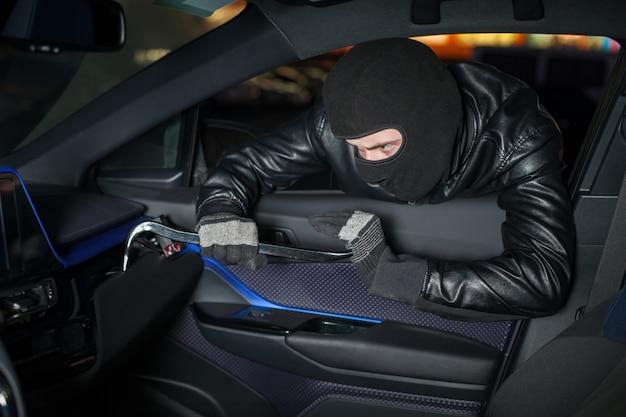 Carjacker открывает перчаточный ящик ломом. мужчина вор с балаклавой на голове рубит машину. концепция опасности угона автомобиля. преступление на транспорте