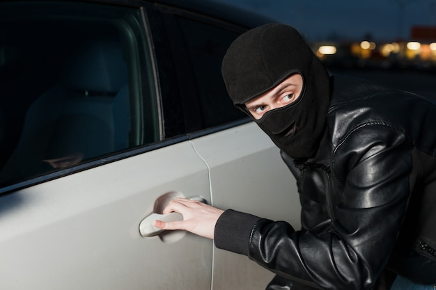 Carjacking danger, car insurance advertising concept. male thief with balaclava on his head trying to open car door. carjacker unlock vehicle