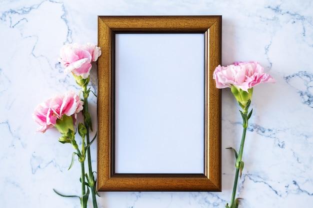 대리석 배경, 발렌타인 데이, 어머니의 날 또는 생일 배경에 빈 그림 프레임에 카네이션 꽃