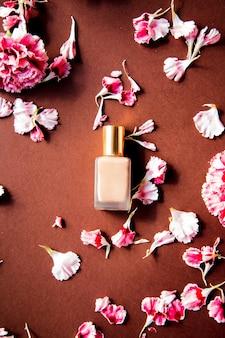 茶色の表面にカーネーションの花びらとファンデーションクリーム。
