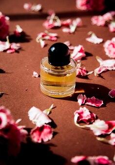 茶色の表面にカーネーションの花びらと香水瓶。