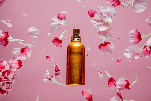 ピンクの背景にカーネーションの花びらと香水瓶。
