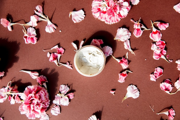 茶色の表面にカーネーションの花びらとスキンケアクリーム。