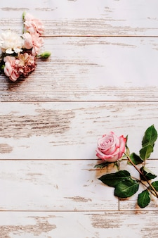 Carnation flowers and pink rose on old wooden table