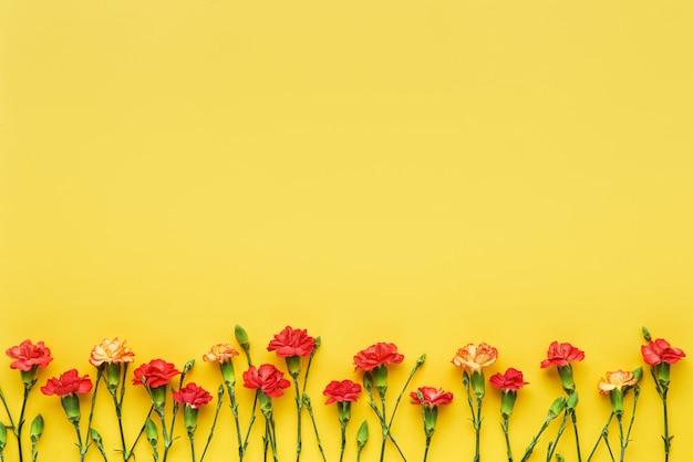 カーネーションの花は黄色の背景に接しています母の日バレンタインデーの誕生日のお祝い