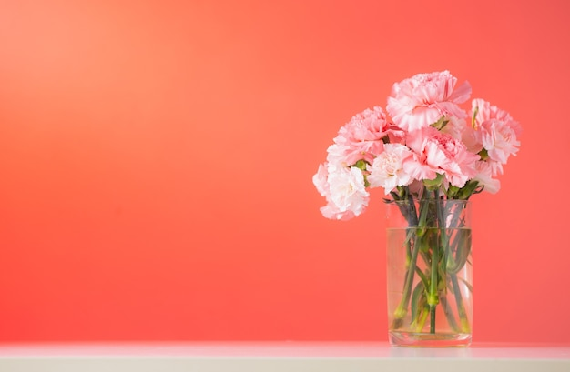 Цветы гвоздики в стеклянной вазе на цветном фоне пышной лавы