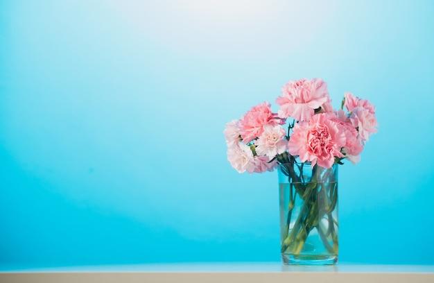 青い壁にカーネーションの花