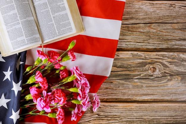 Цветы гвоздики на открытом чтении библии на крупном плане в американском флаге