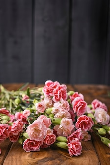 Carnation with pink and white petals on a wooden table.