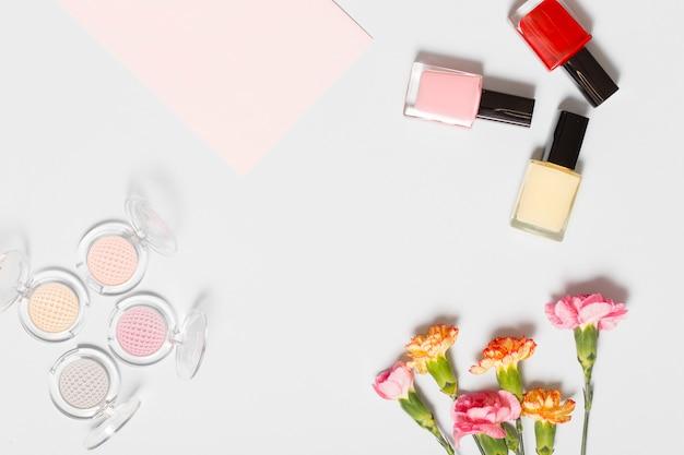 Carnations near eye shadows and nail polishes