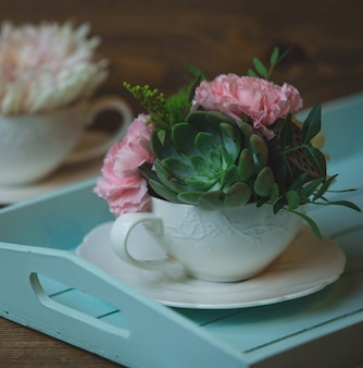 Carnations and suculents in a white ceramic cup