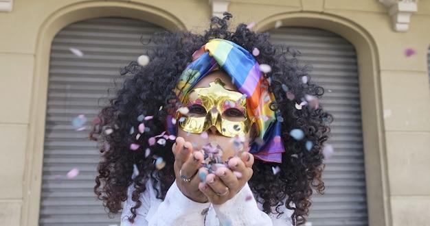 カーニバルパーティー。紙吹雪を吹く衣装を着たブラジルの巻き毛の女性。