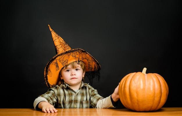 カーニバルコスチュームハッピーハロウィン幼児がトリックをプレイしたり、ハロウィンに隠れている魔女の帽子をかぶった子供を治療したりする