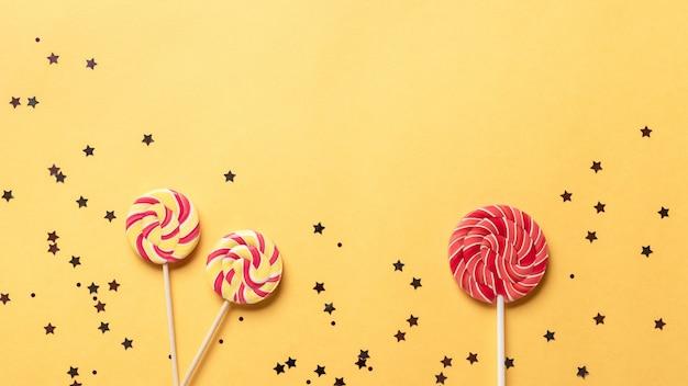 막대 사탕과 빛나는 반짝 카니발, 축제 또는 생일 배경. 노란색 배경. 텍스트를위한 장소입니다. 배너
