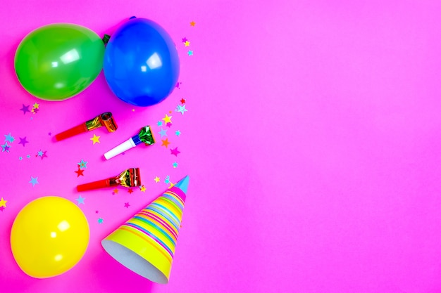 Carnival hats and accessories for birthday celebration lie on bright pink background. Premium Photo