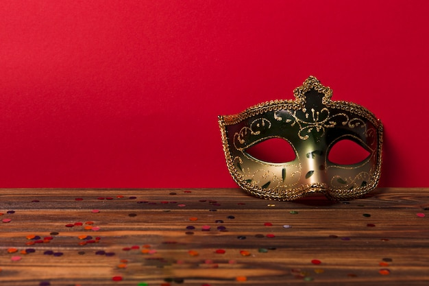 Carnival mask near red wall