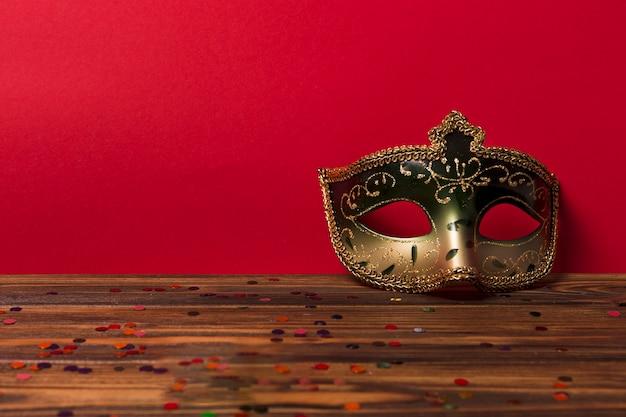 Карнавальная маска возле красной стены